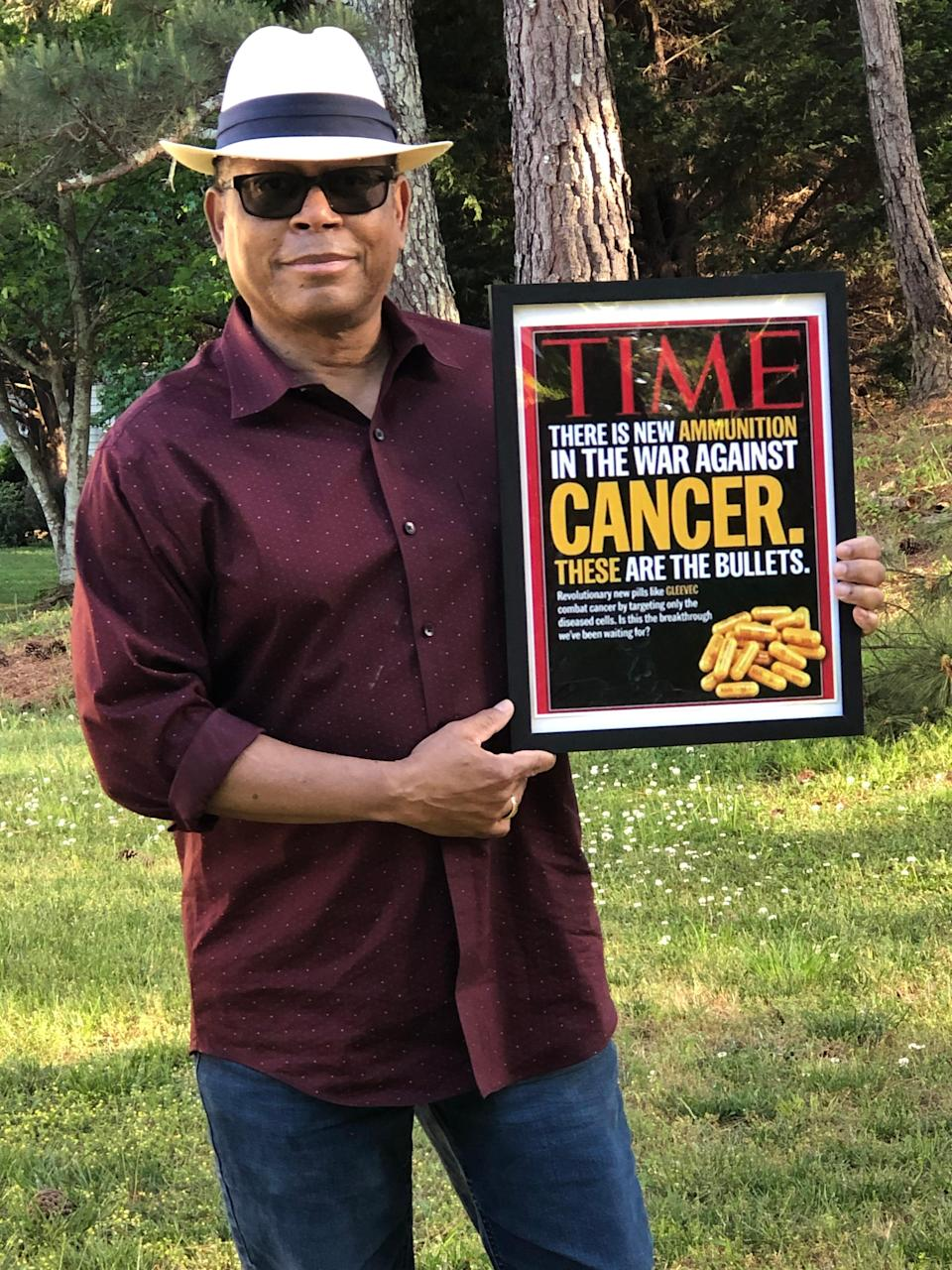 Mel Mann holds up the May 28, 2001 Time magazine, which focused on the cancer drug Gleevec, which saved his life.
