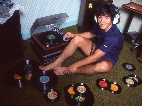Diego Maradona at home with his record collection