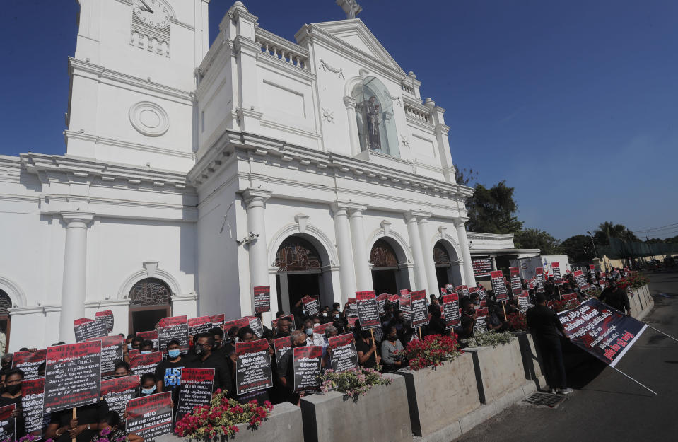 Catholic devotees hold placards during a protest demanding justice for the 2019 Easter Sunday bomb attack victims out side the St. Anthony's church, one of attack sites, in Colombo, Sri Lanka, Sunday, March 7, 2021. (AP Photo/Eranga Jayawardena)
