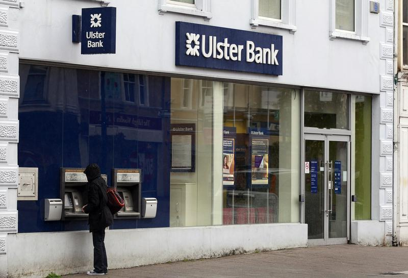 A customer uses a cash machine at a branch of the Ulster Bank in Coleraine, Northern Ireland
