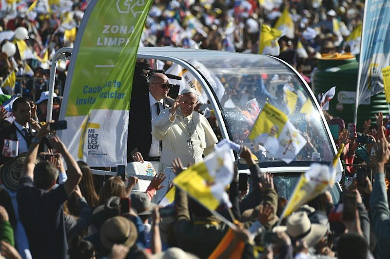 Pope Francis waves from the popemobile as he arrives at Maquehue airport in Temuco to celebrate an open-air mass (AFP Photo/Vincenzo PINTO)
