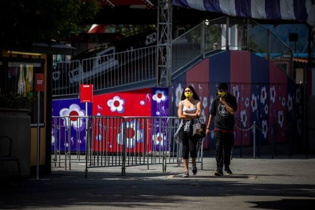 Two people walk through Playland at the PNE in Vancouver on July 10, 2020. (Ben Nelms/CBC - image credit)
