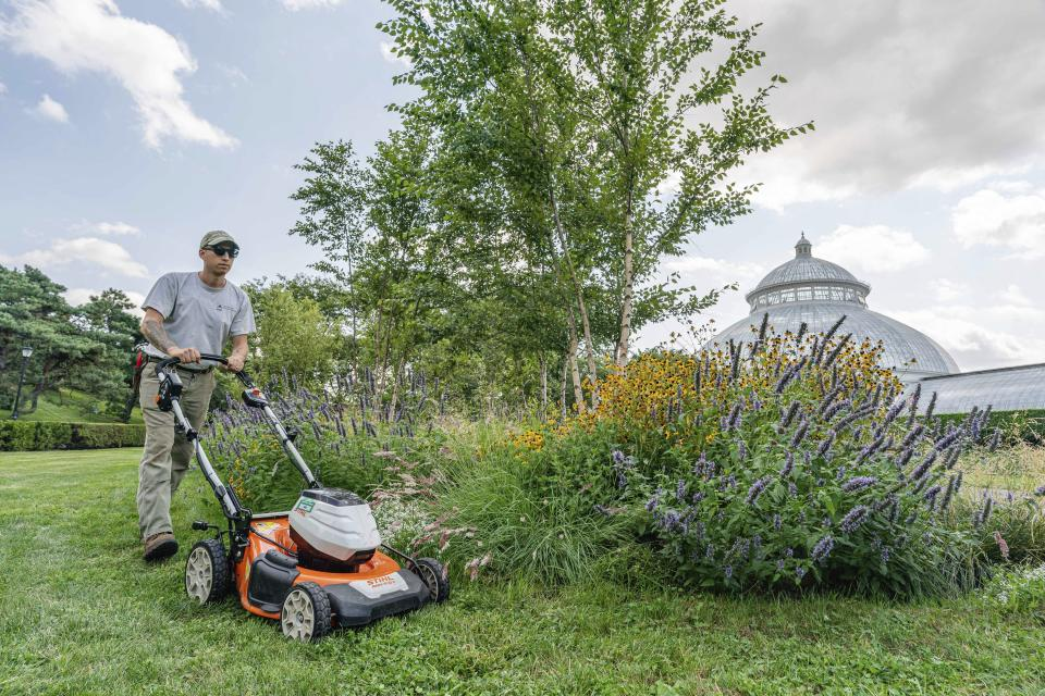 This undated image released by the New York Botanical Garden shows Tyler Campbell mowing the grounds in front of the Enid A. Haupt Conservatory at the New York Botanical Garden in the Bronx borough of New York. (Marlon Co/New York Botanical Garden via AP)