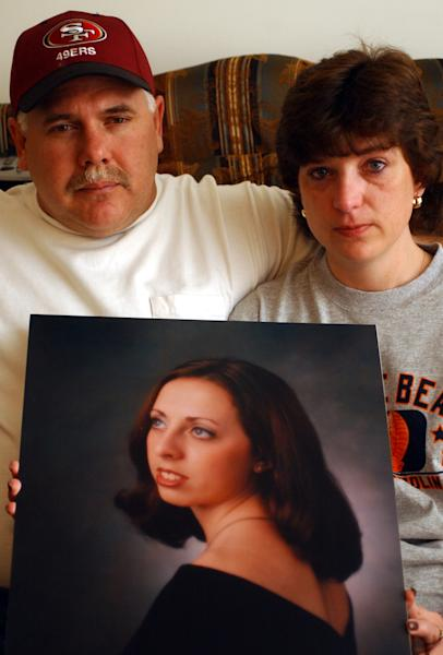 FILE - In a Nov. 8, 2003, file photo, John and Kandi Burns hold a portrait of their daughter Samantha Burns at their home in West Hamlin, W.Va. The FBI moved 36-year-old Chadrick Evan Fulks from the federal penitentiary in Terre Haute, Ind., to West Virginia in March so he could assist in finding the remains of 19-year-old Samantha Nicole Burns, a Marshall University student missing since 2002 and presumed dead. (AP Photo/The Herald-Dispatch, Lori Wolfe, File)