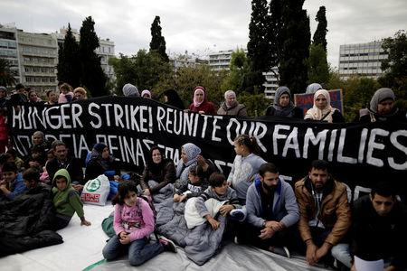 Refugees seeking reunification with family members in Germany sit in front of a banner announcing a hunger strike during a protest near the parliament building in Athens, Greece, November 1, 2017. REUTERS/Alkis Konstantinidis