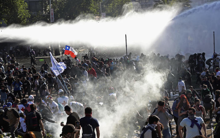 Demonstrators run from police launching water canons and tear gas as a state of emergency remains in effect in Santiago, Chile, Sunday, Oct. 20, 2019. Protests in the country have spilled over into a new day, even after President Sebastian Pinera cancelled the subway fare hike that prompted massive and violent demonstrations. (Photo: Esteban Felix/AP)