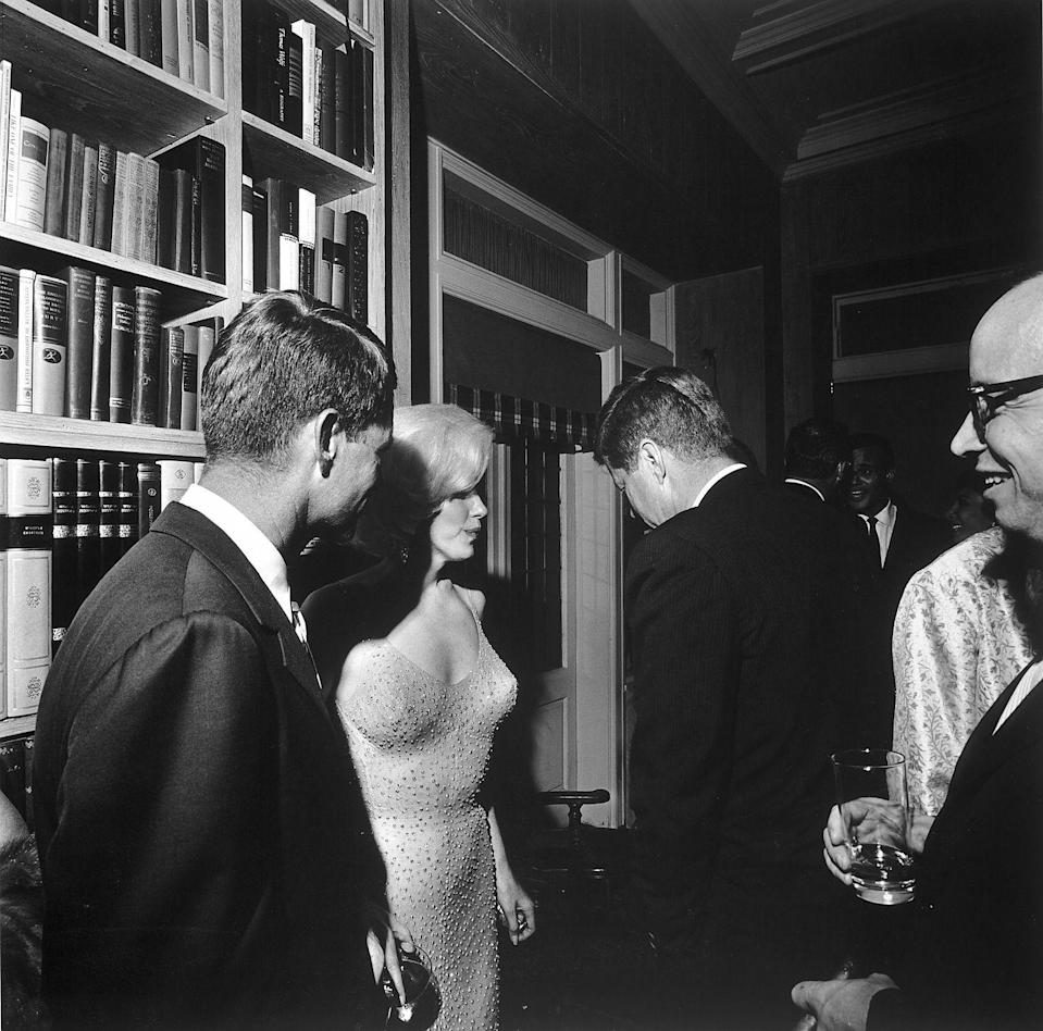 "<p>Marilyn Monroe wears a fitted sequin gown as she speaks with the President and his brother, Robert F. Kennedy, at a New York party in 1962. The fête was an after-party for a political fundraiser held at Madison Square Garden in honor of JFK's birthday, where Monroe famously sang ""Happy Birthday"" to the POTUS.</p>"