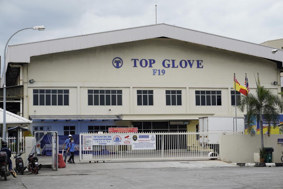 Workers from Top Glove walk out fromTop Glove factory in Shah Alam, Malaysia, Wednesday, Nov. 25, 2020. Malaysia's Top Glove Corp., the world's largest maker of rubber gloves, says it expects a two to four-week delay in deliveries after more than 2,000 workers at its factories were infected by the coronavirus, raising the possibility of supply disruptions during the pandemic. (AP Photo/Vincent Thian)