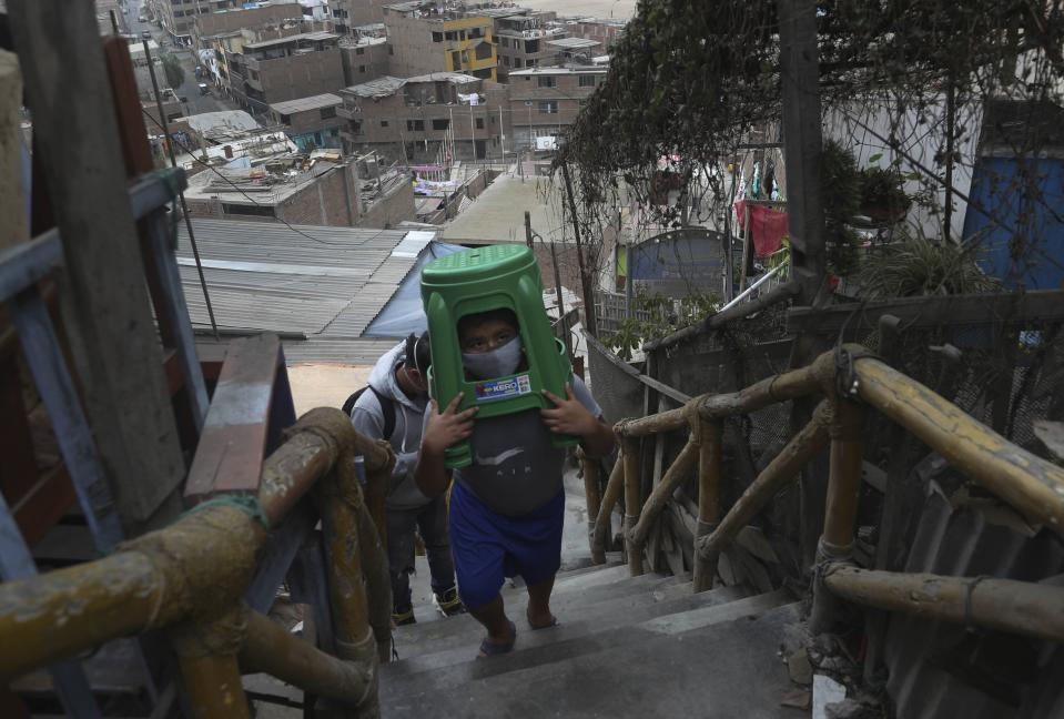 Twelve-year-old Yacdel Flores, hauling hard plastic stools, ascends a flight of stairs to the top of a hill to receive a free haircut from 21-year-old barber Josue Yacahuanca, in the San Juan de Lurigancho neighborhood of Lima, Peru, Friday, June 19, 2020. There are around 150,000 hairdressers in Peru, but Yacahuanca is one of the few who decided to offer his services for free to those most in need amid the new coronavirus pandemic. (AP Photo/Martin Mejia)