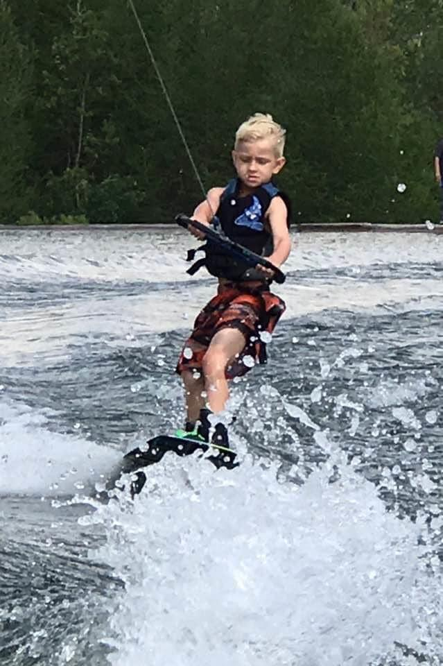 Photo shows Andrew Brady water skiing on a lake.