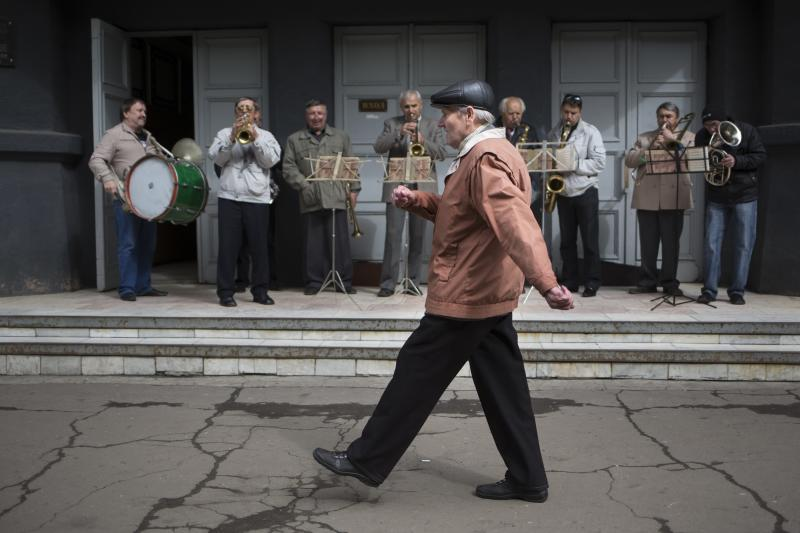 An elderly man marches in front of an amateur band while local citizens gather to mark May Day in Slovyansk, eastern Ukraine, Thursday, May 1, 2014. Russian state news media were quick to dismiss the protests as the work of Ukrainian neo-Nazis, a particularly loaded accusation because Ukrainian nationalists collaborating with the Nazis are blamed for horrific reprisal attacks during World War II. (AP Photo/Alexander Zemlianichenko)