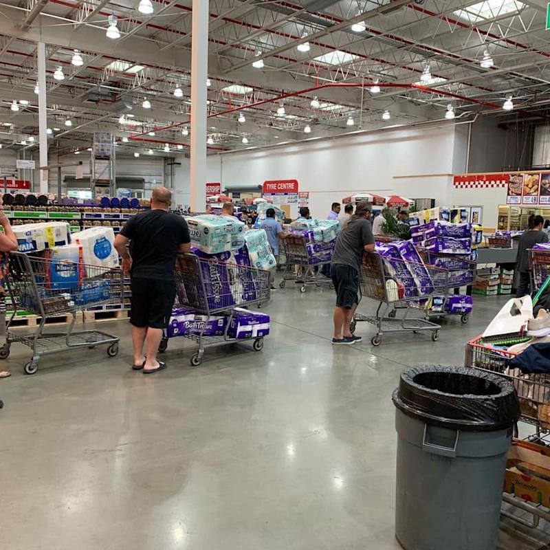 Pictured is a line of people with trolleys filled with toilet paper at Costco, Casula.