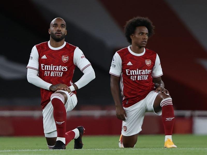 Alexandre Lacazette and Willian of Arsenal take a knee prior to their Premier League fixture against West HamPOOL/AFP via Getty Images