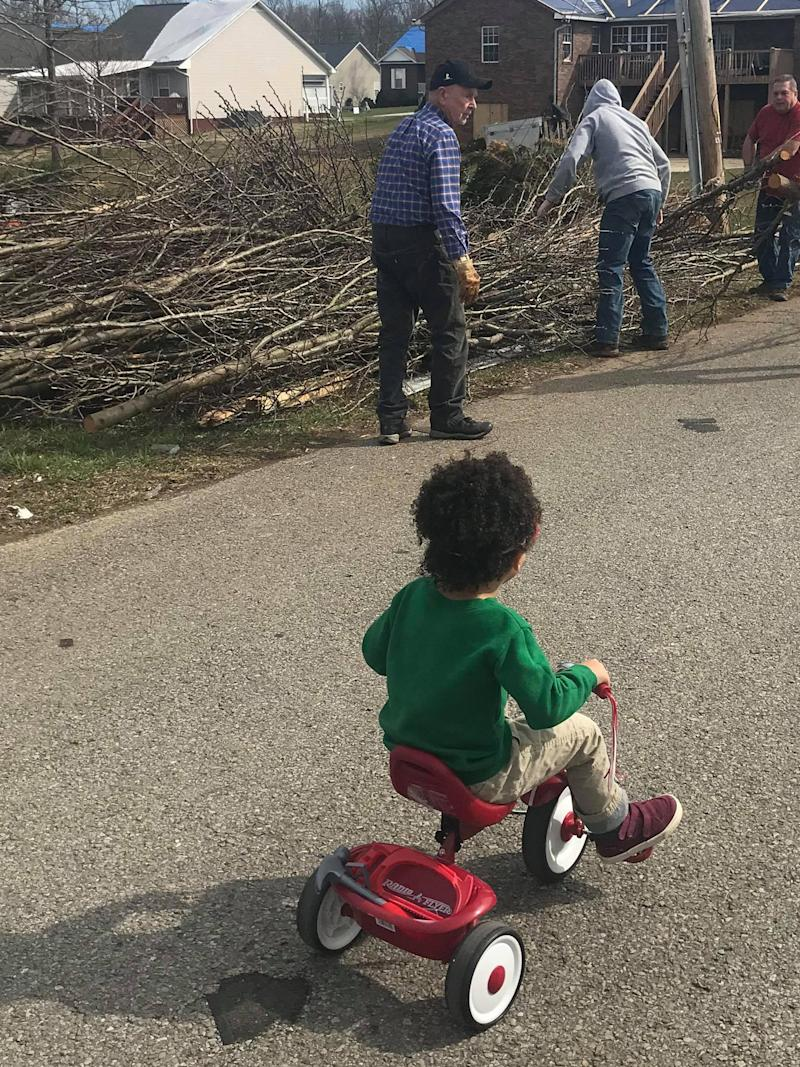 Dax looks at the damage after the tornado Tuesday. (Susan Stout Dyer / WBIR)