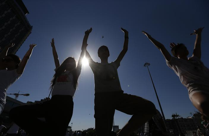 Young people silhouetted against the sun practice yoga during a silent protest at Taksim Square in, Istanbul, Turkey, Wednesday, June 19, 2013. After weeks of sometimes-violent confrontation with police, Turkish protesters have found a new form of resistance: standing still and silent. (AP Photo/Petr David Josek)