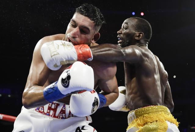 Terence Crawford, right, punches England's Amir Khan during the fifth round of a WBO world welterweight championship boxing match Sunday, April 21, 2019, in New York. Crawford won the fight. (AP Photo/Frank Franklin II)