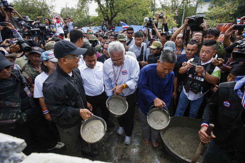 Anti-government protest leader Suthep Thaugsuban (C) prepares to pour cement to block a gate of the Government House during a rally in Bangkok February 17, 2014. Thousands of protesters seeking to oust Thai Prime Minister Yingluck Shinawatra surrounded the government's headquarters in Bangkok on Monday, in a defiant riposte to police efforts to begin retaking sites they have been occupying for weeks. REUTERS/Athit Perawongmetha (THAILAND - Tags: POLITICS CIVIL UNREST)