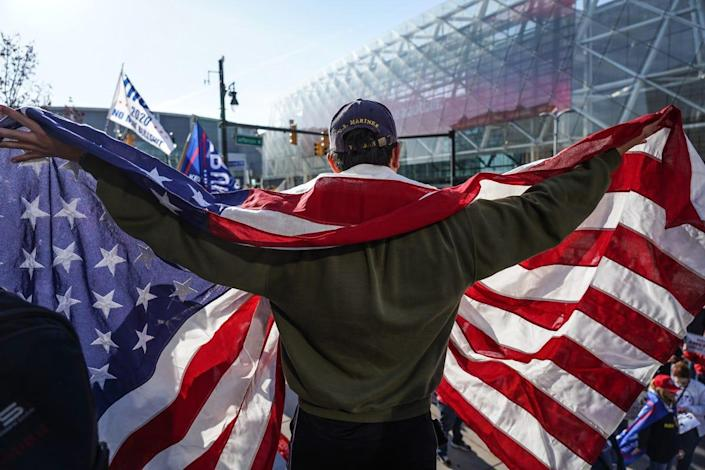 Michael Foy of Wixom, Michigan, holds his flag open while standing above the crowd gathered for a rally in support of President Trump outside of the TCF Center in Detroit on Friday, Nov 6, 2020 where the absentee ballot count for the city of Detroit took place.