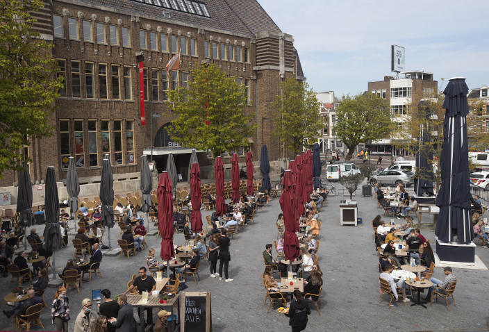 Guests queue, bottom, to take their seats at spaced out terrace tables in Utrecht, Netherlands, Wednesday, April 28, 2021. The Netherlands became the latest European country to begin cautiously relaxing its lockdown even as infection rates and intensive care occupancy remain stubbornly high. The Dutch follow Italy, Greece, France and other European nations in moving to reopen society and edge away from economically crippling lockdowns in the coming weeks.(AP Photo/Peter Dejong)