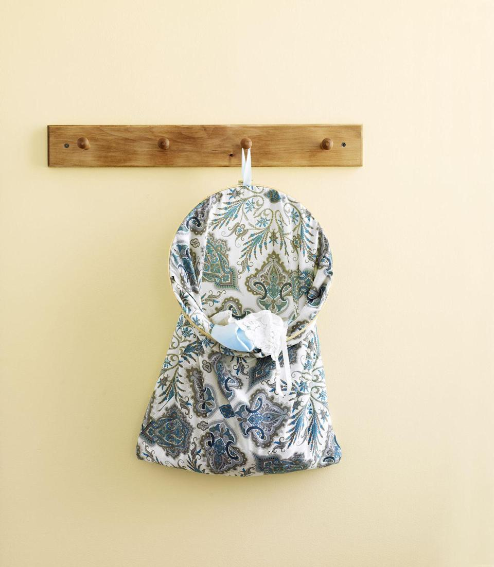 <p>This patterned laundry bag, made with fabric, ribbon, and an embroidery hoop, will keep your delicates in one spot. To make, clamp the pillowcase into the hoop, tie on a loop of ribbon to the hoop's clamp, and hang near your hamper.</p>