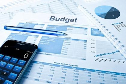 Budget Figures With Calculator And Pen Getty