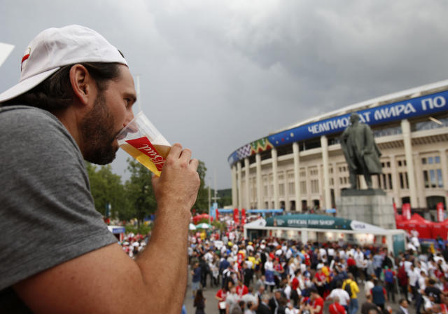 "In this July 11, 2018 photo, a man drinks a beer in a Budweiser pavilion in front of the Lenin statue and the Luzhniki Stadium as fans arrive for the semifinal match between Croatia and England, during the 2018 soccer World Cup in Moscow, Russia. When Lenin had a thirst for revolution, this is not what he had in mind. Fans attending Sunday's World Cup final between France and Croatia will pass a huge statue of the Bolshevik Revolution's leader as they enter Luzhniki Stadium. Abutting the rear of the monument is a Budweiser concession stand with a sign proclaiming: ""Drink smart today _ celebrate tomorrow.""(AP Photo/Rebecca Blackwell)"