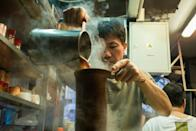 """A tea master makes a milk tea -- or """"lai cha"""" -- a tangy brew made from blends of black tea strained repeatedly through a sock-like cloth, at a tea shop in Hong Kong's Central district on August 10, 2016"""