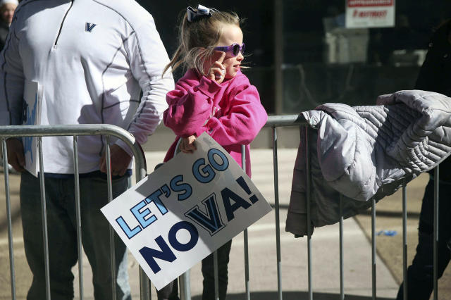 Avery Gergel, 6, of Pottstown, whose father is a Villanova graduate, makes a V sign along Market Street before Villanova's NCAA men's basketball tournament victory parade, Thursday, April 5, 2018, in Philadelphia. (Tim Tai/The Philadelphia Inquirer via AP)