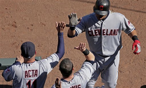 Cleveland Indians' Carlos Santana, right, celebrates as he comes into the dugout after hitting a two-run home run during the sixth inning of a baseball game against the Kansas City Royals, Sunday, Sept. 23, 2012, in Kansas City, Mo. (AP Photo/Charlie Riedel)