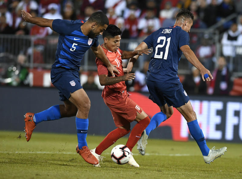 United States' Cameron Carter-Vickers (5) , and United States' Aaron Long (21) , rpressure Peru's Raul Ruidiaz (11) during the first half of an international friendly soccer match in East Hartford, Conn., Tuesday, Oct. 16, 2018. (AP Photo/Jessica Hill)