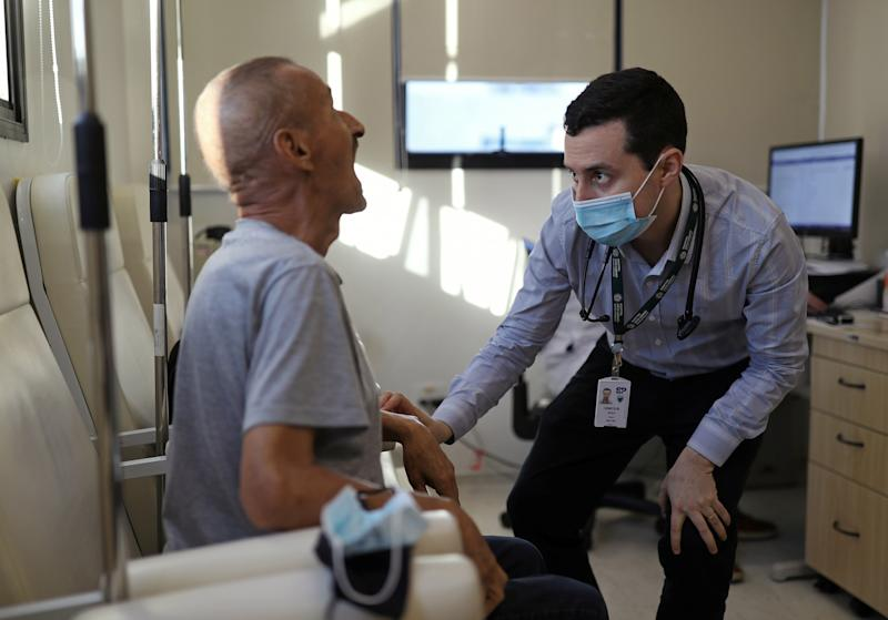Image: Vinicius Molla, a hematologist and volunteer of the clinical trial of Oxford COVID-19 vaccine, examines a patient at a consulting room in Sao Paulo, Brazil (Amanda Perobelli / Reuters)