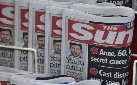 Copies of The Sun newspaper are seen on a newsstand outside a shop in central London