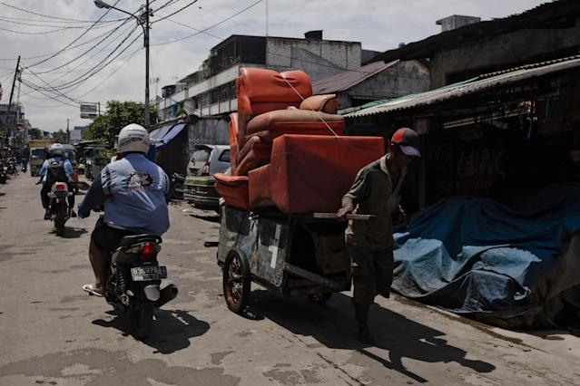 JAKARTA, INDONESIA - JANUARY 26: A man carries furniture by a cart as people clean up their homes after the flood in North Jakarta on January 26, 2013 in Jakarta, Indonesia. With heavy rain forecast for January 26-28, Indonesian authorities have organised the use of generators and cloud-seeding measures to defuse rain-laden clouds to help prevent further flooding of Jakarta, following last week's floods which claimed the lives of 32 people. (Photo by Ulet Ifansasti/Getty Images)