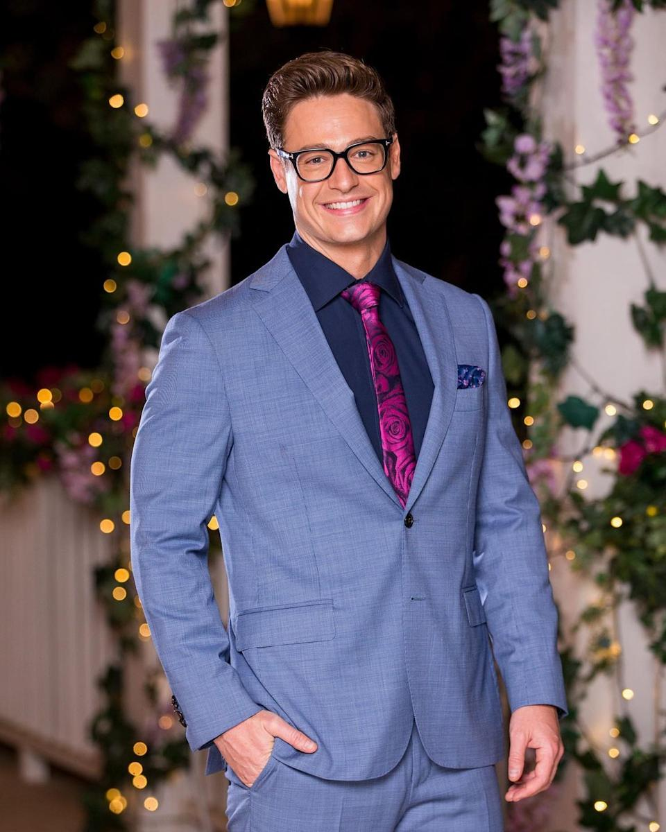 Matt Agnew wearing a blue suit and red rose print tie on set of The Bachelor in 2019