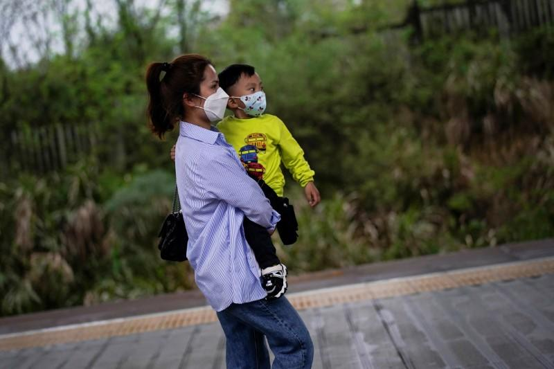 Chen Ting, 28, and her 3 years old son wear face masks at a railway station in Xianning of Hubei province