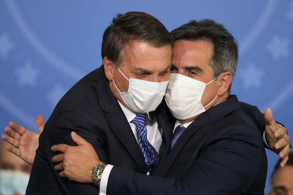 Brazil's President Jair Bolsonaro, left, embraces his new Chief of Staff Ciro Nogueira during Nogueira´s swearing-in ceremony at the Planalto presidential palace, in Brasilia, Brazil, Wednesday, Aug. 4, 2021. (AP Photo/Eraldo Peres)