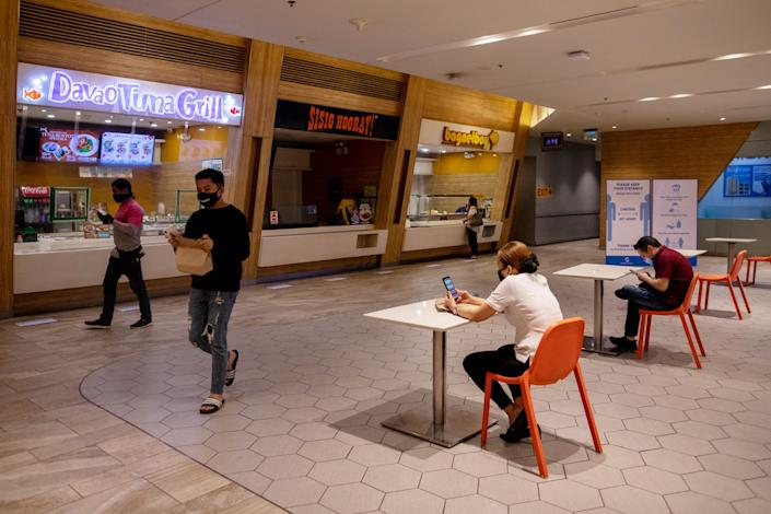"""Diners wait for their orders at a food court where only one customer per table is allowed in Metro Manila, Philippines, on June 16, 2020. <p class=""""copyright"""">REUTERS/Eloisa Lopez</p>"""