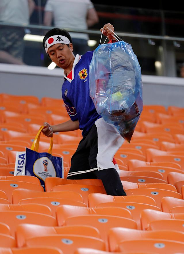 Soccer Football - World Cup - Group H - Japan vs Senegal - Ekaterinburg Arena, Yekaterinburg, Russia - June 24, 2018 Japan fan cleans up after the match REUTERS/Andrew Couldridge