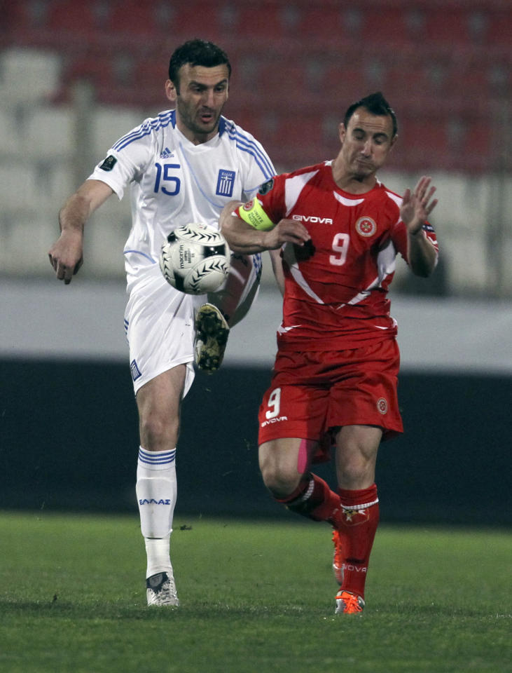 Michael Mifsud of Malta, right, fights for the ball with Vassilis Torosidis of Greece during their Euro 2012 Group F qualifying soccer match at the Ta'Qali national stadium, near Valletta, Malta Saturday, March 26, 2011.