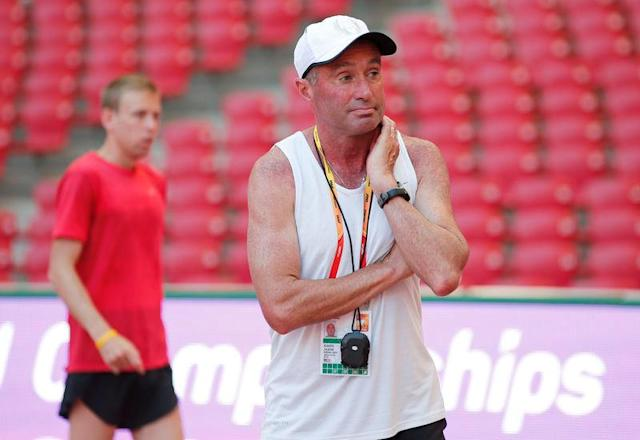 Coach Alberto Salazar stands in front of Galen Rupp of the U.S.A. in the Bird's Nest Stadium at the Wold Athletics Championships in Beijing