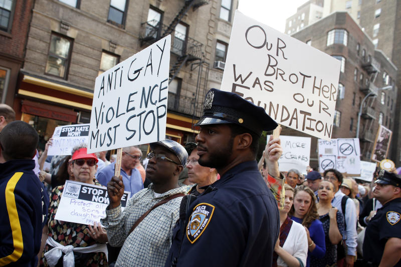 Police look on as members of the LGBT community and their supporters gather to speak out after a string a bias attacks, including the fatal shooting of 32-year old Mark Carson on Saturday, during a rally in New York's Greenwich Village, Monday, May 20, 2013. A spate of hate-fueled attacks on gay men in New York, including a killing last week on a busy street in one of Manhattan's most gay-friendly neighborhoods, has prompted outcry and soul-searching about enduring bias after gay-rights advances in recent years. (AP Photo/Jason DeCrow)
