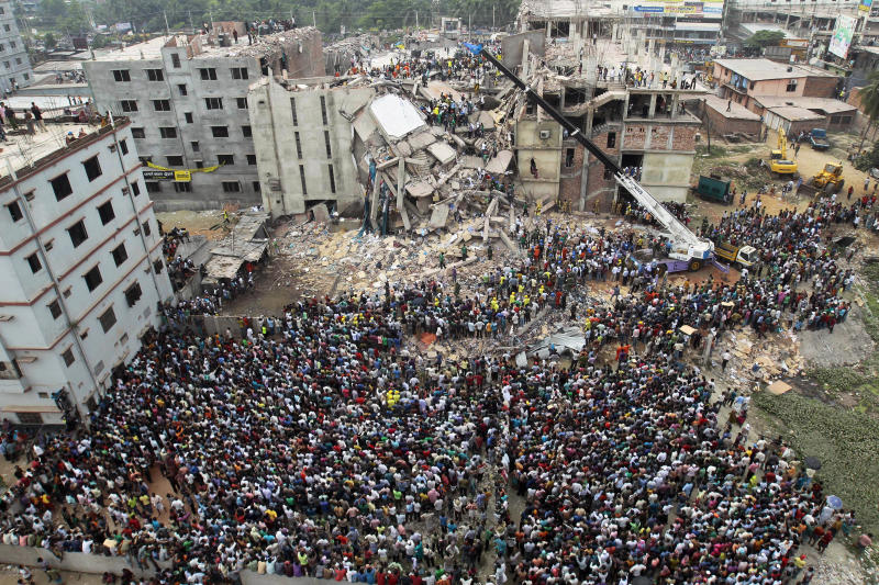 FILE - In this April 25, 2013, file photo, Bangladeshi people gather as rescuers look for survivors and victims at the site of the Rana Plaza building that collapsed a day earlier, in Savar, near Dhaka, Bangladesh. A group set up by European clothing brands that has monitored factory safety in Bangladesh for years plans to leave, with its duties being assumed by a local group including unions and industry figures in the world's second-largest garment manufacturer. The European group and a separate North American group were formed after the collapse in 2013 of Rana Plaza, a building housing five garment factories that made clothing for international brands, that killed at least 1,134 people. The departure, which officials said Thursday, Jan. 16, 2019, was planned for May, follows a protracted tussle with garment manufacturers who wanted Bangladesh's government to form a local watch group to monitor the sector. (AP Photo/A.M.Ahad, File)