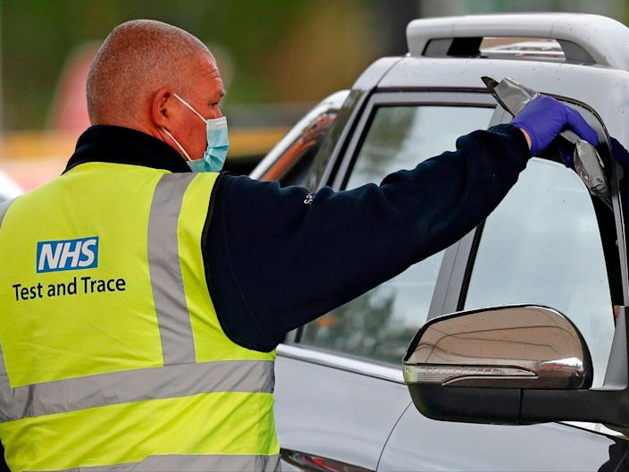 A driver receives a Covid-19 self-test kit from a worker wearing an NHS Test and Trace branded Hi-Vis jacket at a drive-in testing facility in Chessington (AFP via Getty Images)