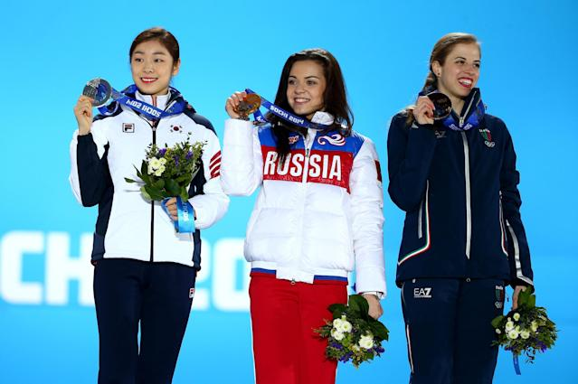 SOCHI, RUSSIA - FEBRUARY 21: (L-R) Silver medalist Yuna Kim of South Korea, Gold medalist Adelina Sotnikova of Russia and Bronze medalist Carolina Kostner of Italy celebrate during the medal ceremony for the Women's Free Figure Skating on day fourteen of the Sochi 2014 Winter Olympics at Medals Plaza on February 21, 2014 in Sochi, Russia. (Photo by Streeter Lecka/Getty Images)