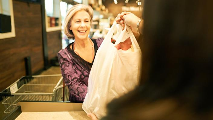 Shot of a mature woman taking a shopping bag from the cashier at a supermarket.