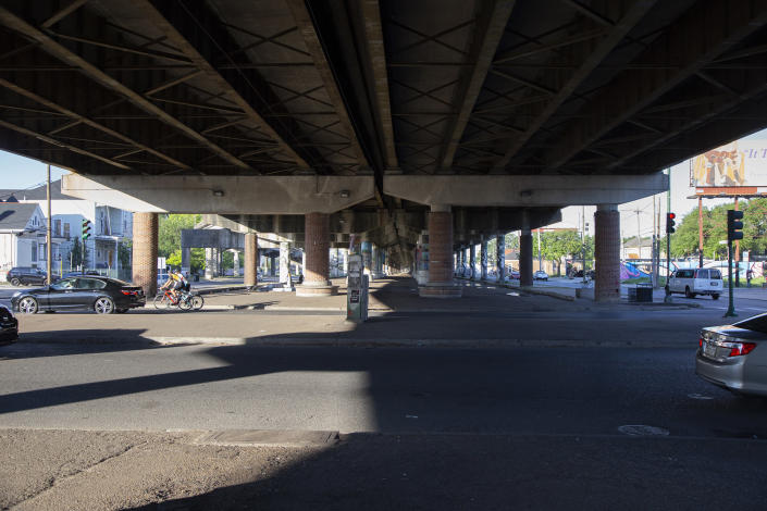 """The elevated freeway running along Claiborne Avenue in New Orleans crosses over Esplanade Avenue in this photo taken on May 7, 2021. Black businesses and culture thrived under a canopy of oak trees along Claiborne Avenue until the late 1960s, when the freeway was built directly on top of it — ripping up the trees and tearing apart a street sometimes called the """"Main Street of Black New Orleans."""" (AP Photo/Rebecca Santana)"""