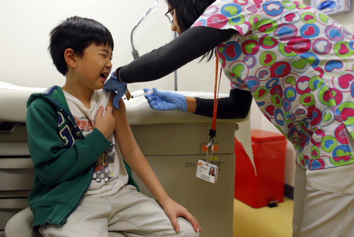 Chihn Ha, eight year old, gets an influenza vaccine injection from nurse Nho Nguyen (R) during a flu shot clinic at Dorchester House, a health care clinic, in Boston, Massachusetts January 12, 2013. Influenza has officially reached epidemic proportions in the United States, with 7.3 percent of deaths last week caused by pneumonia and the flu, the U.S. Centers for Disease Control and Prevention said on January 11.   REUTERS/Brian Snyder    (UNITED STATES - Tags: HEALTH SOCIETY)