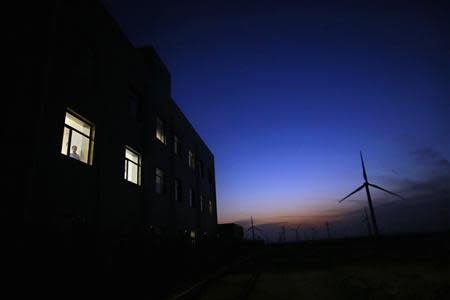 A man stands at the window of a building near a wind turbine used to generate electricity, at a wind farm in Guazhou, 950km (590 miles) northwest of Lanzhou, Gansu Province September 15, 2013. REUTERS/Carlos Barria