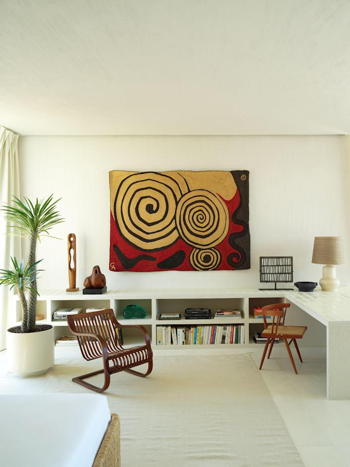 An Alexander Calder tapestry hangs in the primary bedroom. Brass-and-bamboo armchair by Ubunji Kidokoro; grass-seated desk chair by George Nakashima woodworkers.