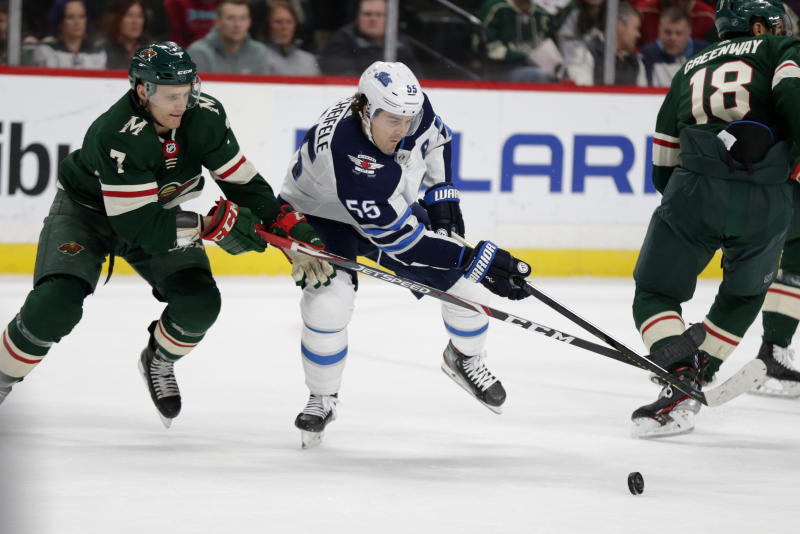 Winnipeg Jets center Mark Scheifele (55) and Minnesota Wild Nico Sturm (7) battle for the puck in the second period of an NHL hockey game Saturday, Dec. 21, 2019, in St. Paul, Minn. (AP Photo/Andy Clayton-King)